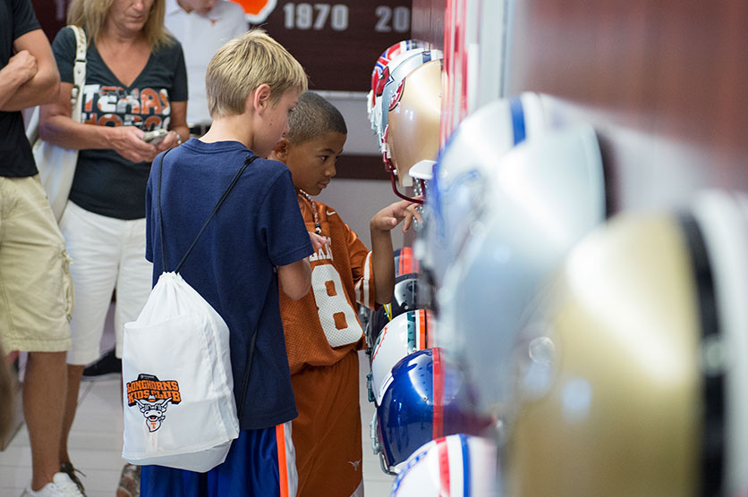 Two young fans admire football helmets