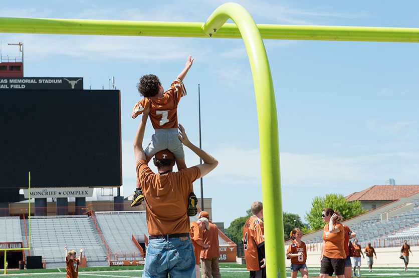 A dad holds his son on his shoulders to touch the goal posts