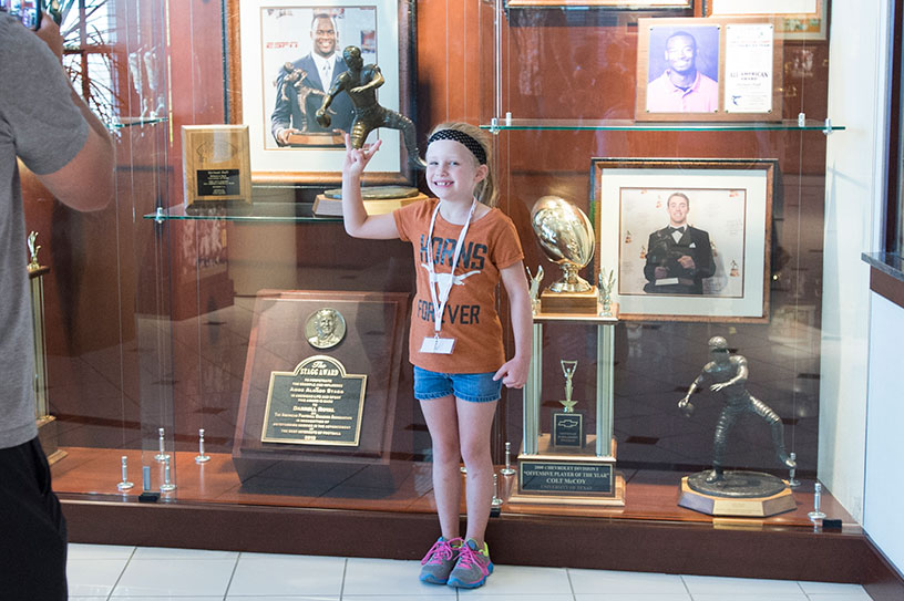 Girls stands in front of a trophy case